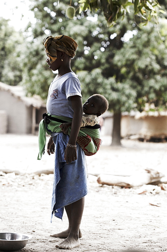 Girl carrying a baby on back, Magadala, Mali