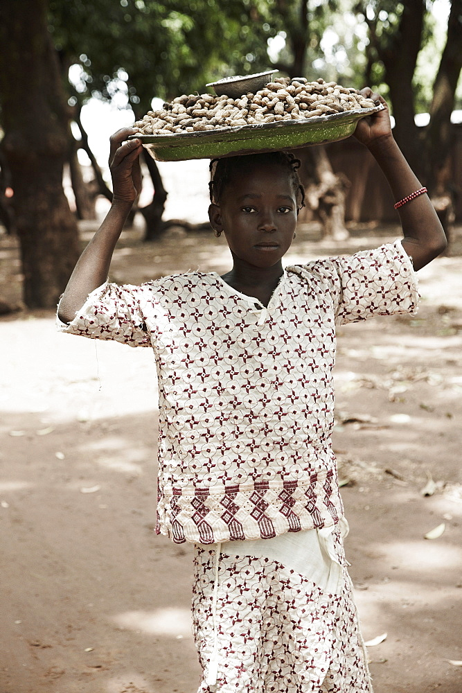 Girl carrying on head a tray with peanuts to market, Yanfolila, Sikasso Region, Mali