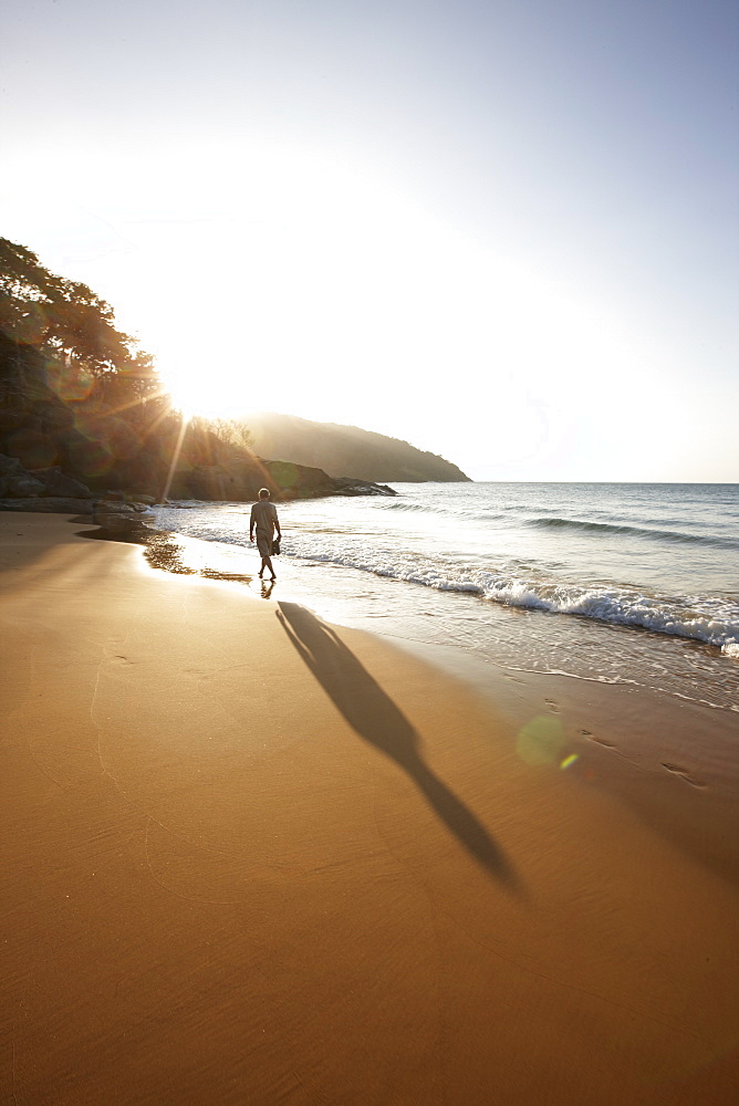 Man walking along Dam Trau beach in the evening, Con Dao Island, Con Dao National Park, Ba Ria-Vung Tau Province, Vietnam