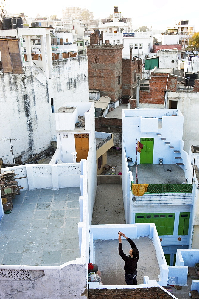 View across rooftops with Hindu doing a religious ceremony in the morning, Udaipur, Rajasthan, India