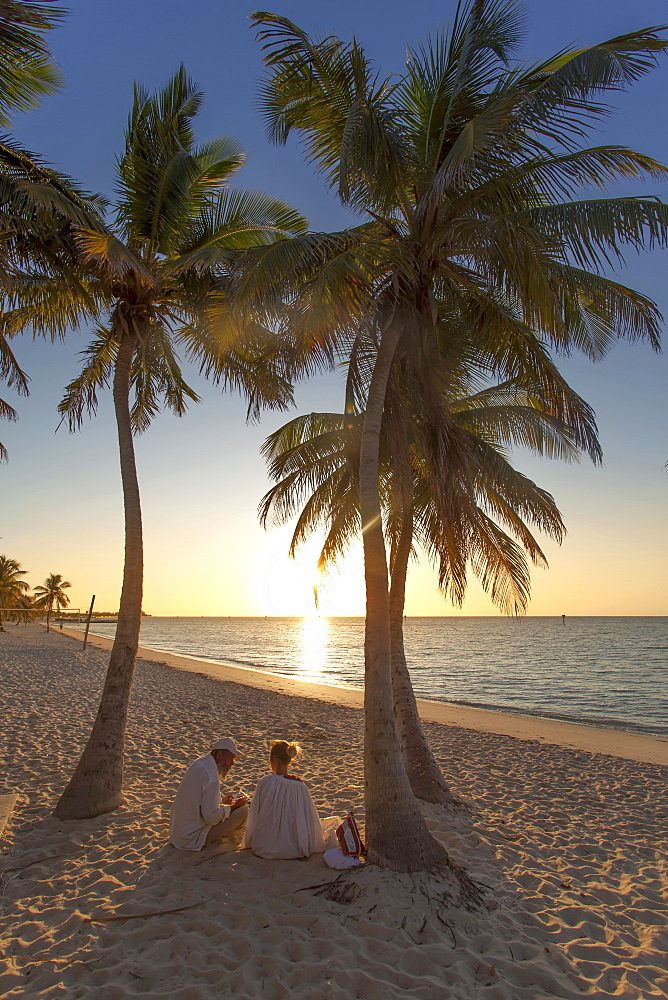Couple sitting at sunrise on Key West Smathers Beach, Key West, Florida Keys, Florida, USA