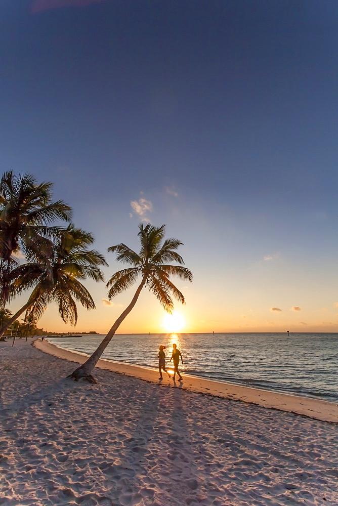 Morning impression with couple jogging along the beach at sunrise, Key West Smathers Beach, Key West, Florida Keys, Florida, USA