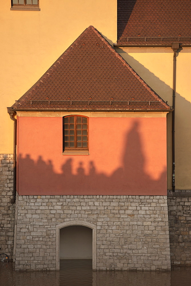 Shadow of people on the old Main bridge reflecting on a house fascade, flooding, Wuerzburg, Franconia, Bavaria, Germany