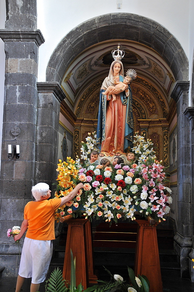 Madonna figure being decorated with flowers, Provocao, Island of Sao Miguel, Azores, Portugal