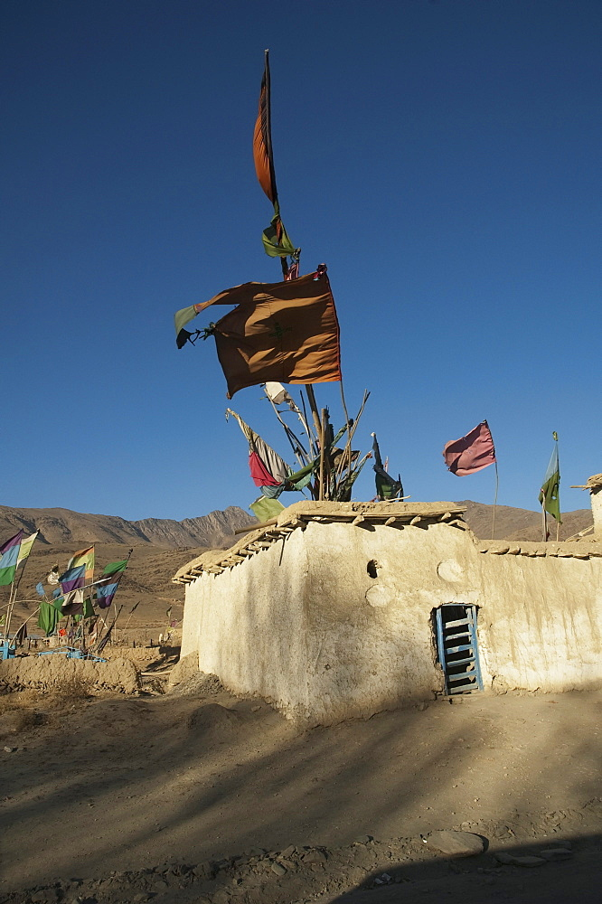 Flags fluttering in the wind over the Shrine of Khoja Mohammad Baba near Jalrez, Vardak Province, Afghanistan