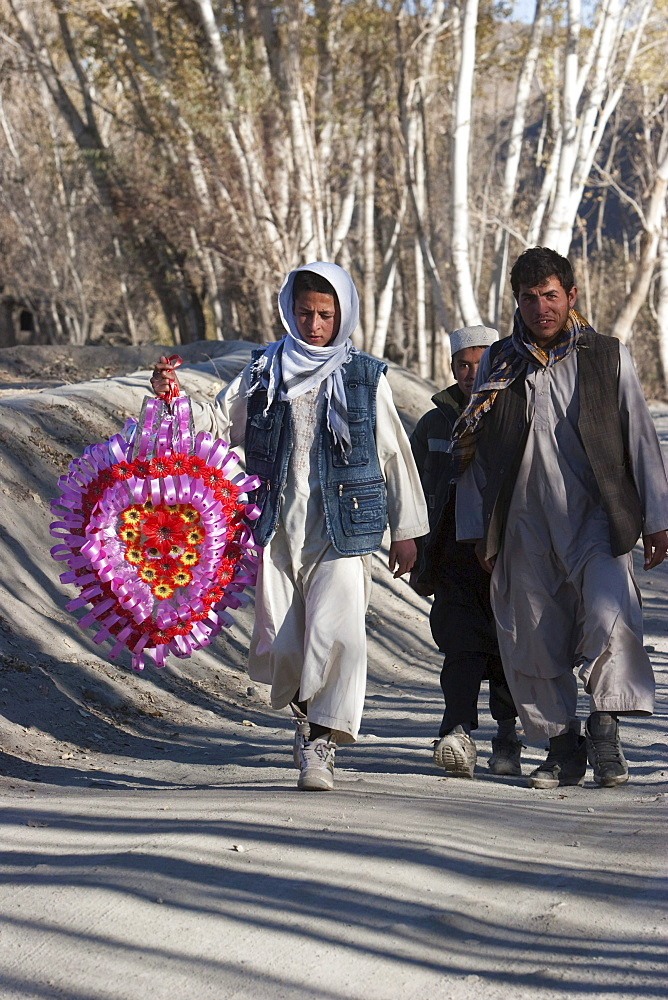 Afghan man and boys carrying a wedding ornament on the road to Tajekha, Vardak Province, Afghanistan