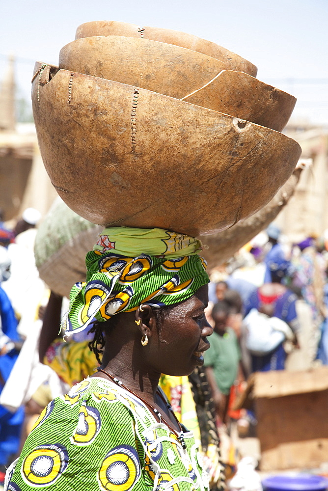 Woman carrying a calabash on her head at the Monday Market, Djenne, Mali