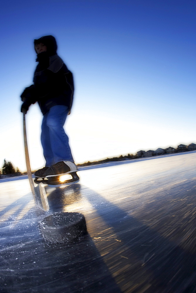 Boy Ice Skating on Lake with Hockey Stick and Puck, Calgary, Alberta