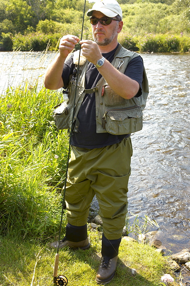 Man Preparing Rod for Fly Fishing, Grand River, Ontario