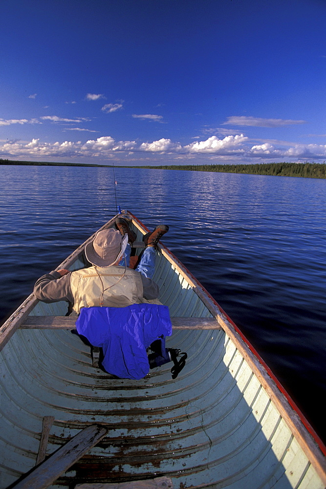 Man Relaxing in Canoe, Sutton Lake, Northern Ontario