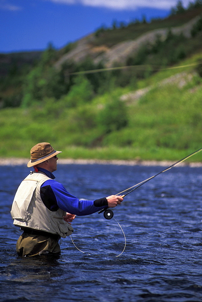 Fly Fisherman Casts into Northern Ontario River