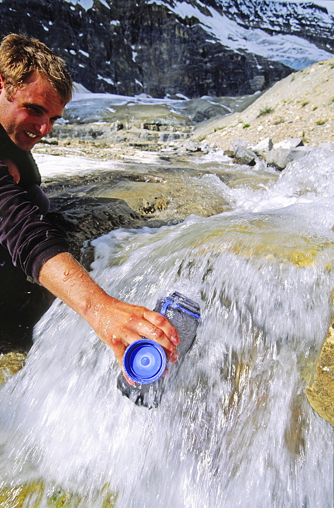 Filling a Water Bottle in a Glacial Stream, Iceline Trail, Yoho National Park, British Columbia