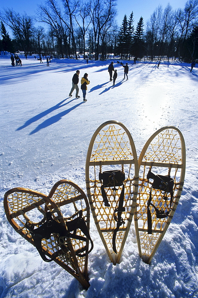 Snowshoes with Ice Rink and Skaters in the background, St. Vital Park, Winnipeg, Manitoba