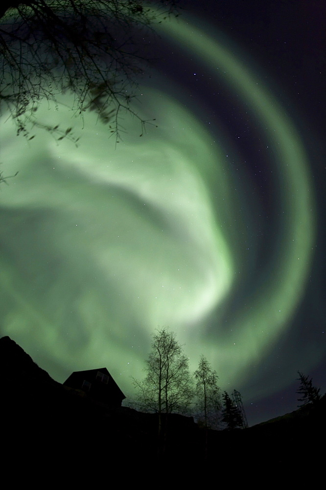 Swirling aurora borealis fills the night sky on the outskirts of the capital city of Yellowknife, Northwest Territories, Canada.