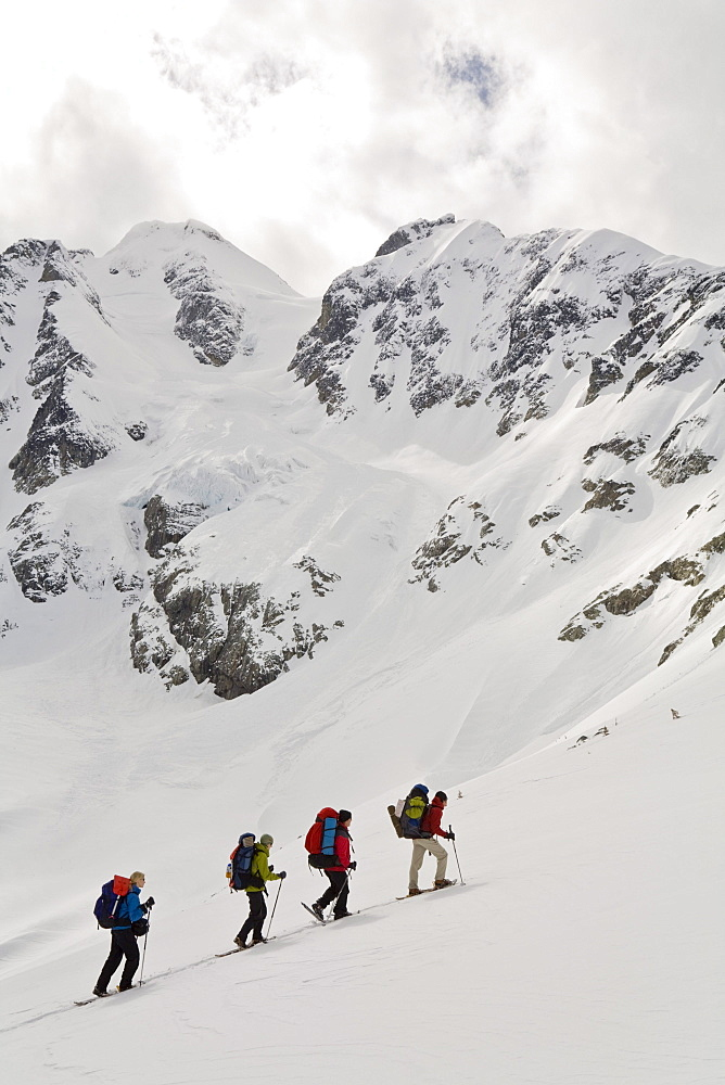 Snowshoers ascend to Vantage Pass with Anniversary Glacier and Joffre Peak in background, British Columbia