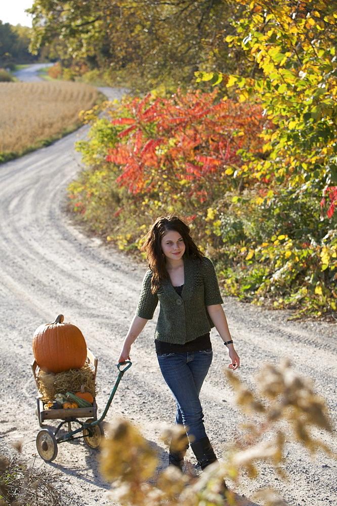 Teenage girl pulling wagon with pumpkin along path, Vittoria, Ontario
