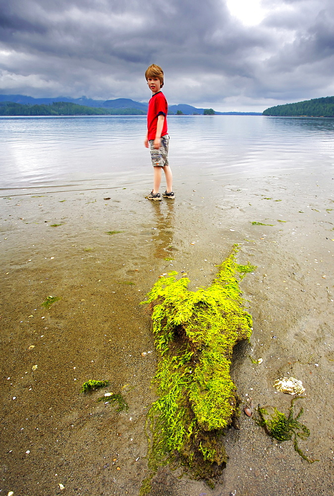 Young boy standing on a beach, Barkley Sound, Vancouver Island, British Columbia