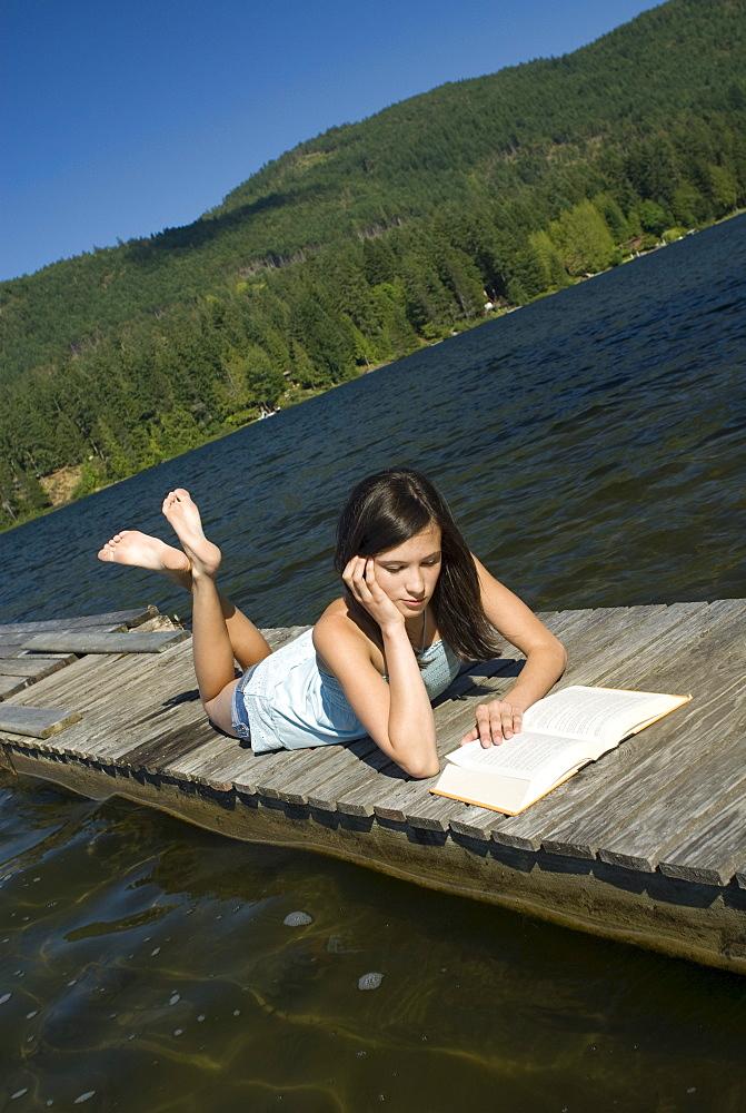 Teenager reading on a dock, Shawnigan Lake, Victoria, British Columbia