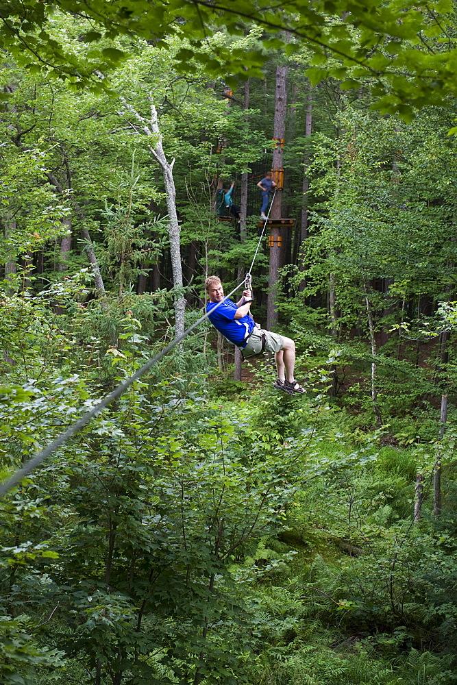 Man on a zip line between trees, Arbres en Arbres, Shawinigan, Quebec