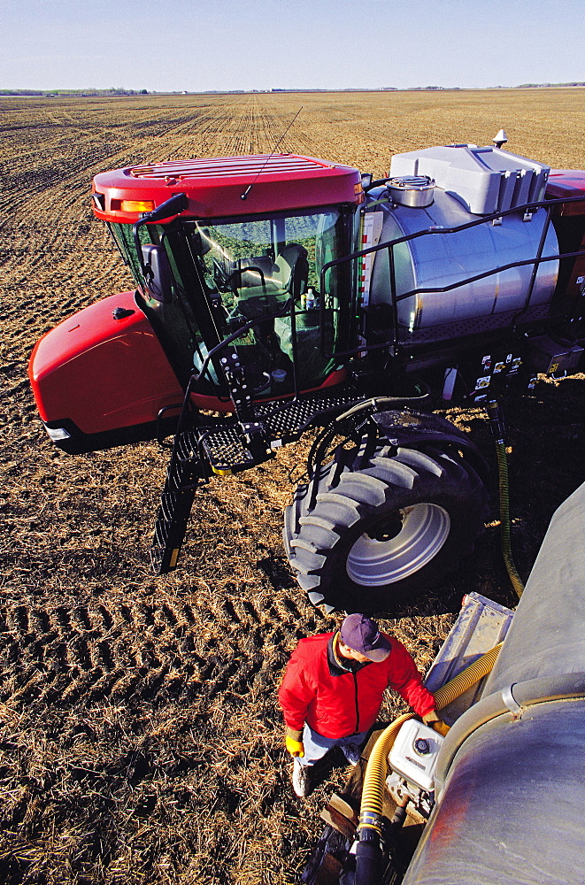Farmer loads high Clearance Sprayer with liquid Fertilizer for application to a recently Seeded Wheat Field, near Dugald, Manitoba