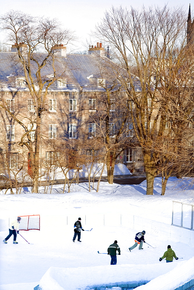 People playing hockey on an outside skating rink in winter, Quebec city