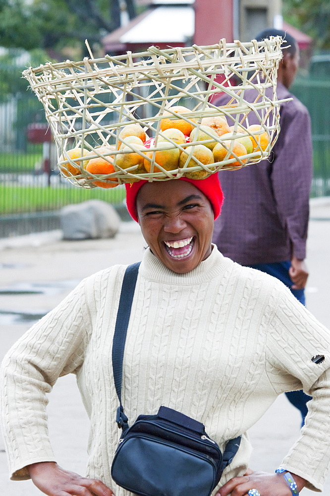 Woman carrying a basket with oranges on her head in Antananarivo, Madagascar