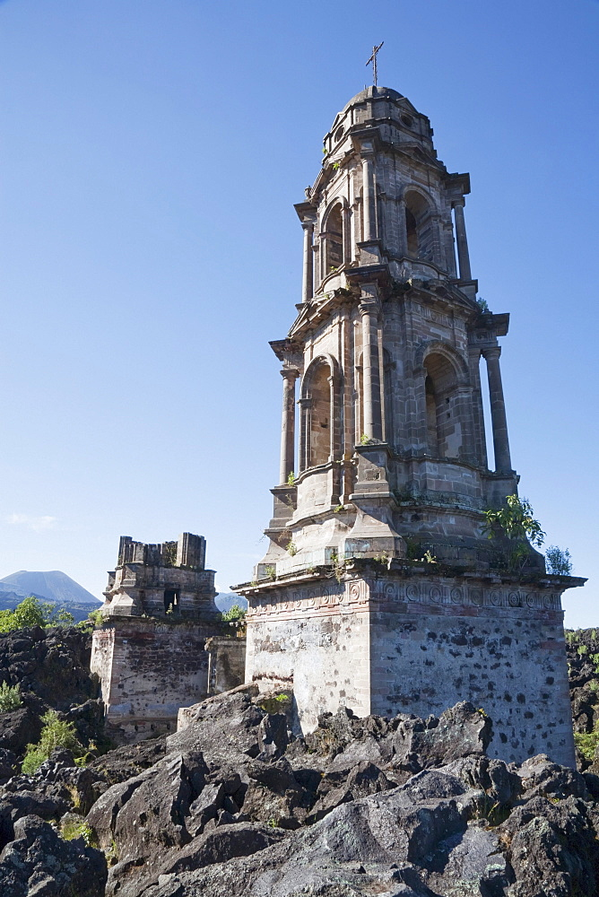 The bell tower of the San Juan Parangaricutiro Church sticks out through the Paricutín Volcano lava flow, Michoacán, Mexico