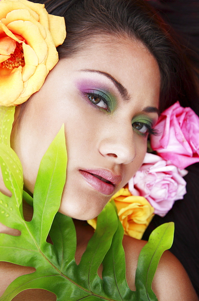 Hawaii, Oahu, Fashion model poses among flowers and leaf.