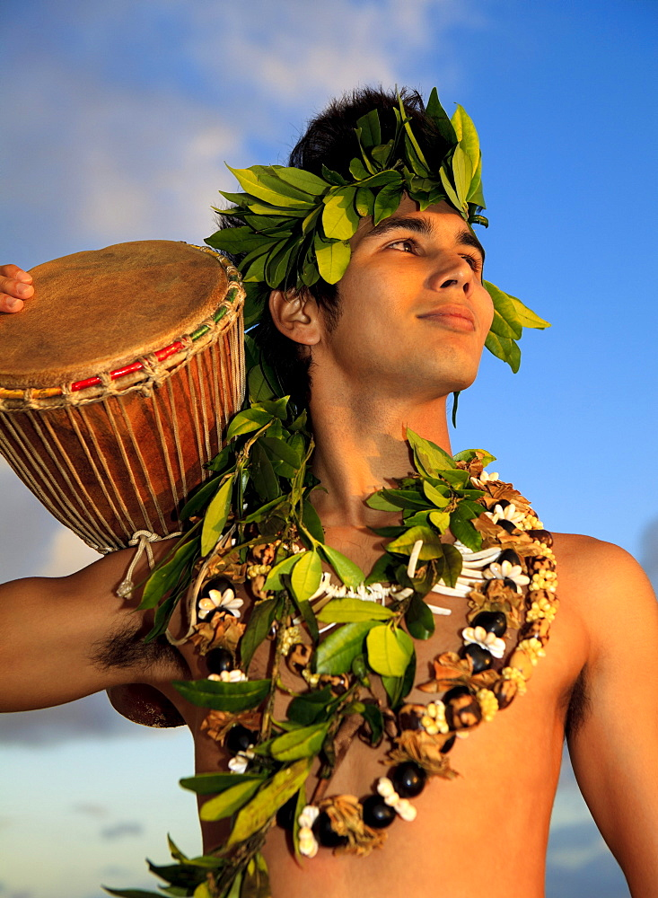 Hawaii, Oahu, Polynesian man with drum along coast, Sunrise light.