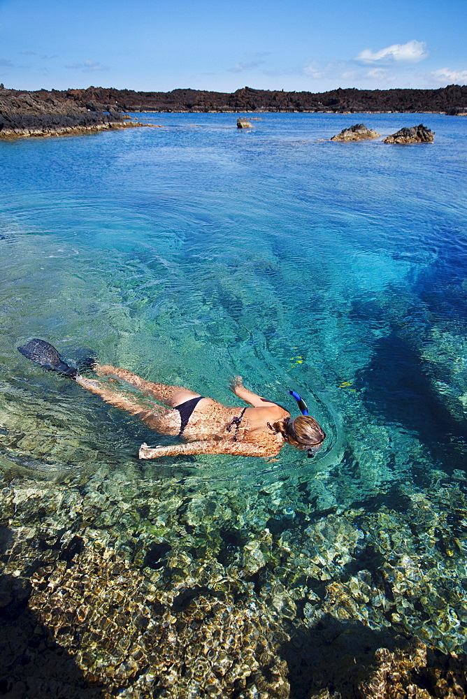 Hawaii, Maui, Laperouse Bay, Woman snorkeling in shallow clear water over coral reef