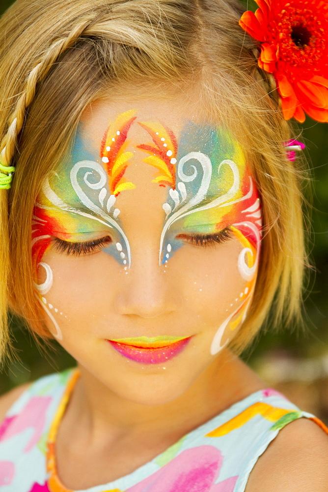 Hawaii, Young girl wearing colorful facepaint.