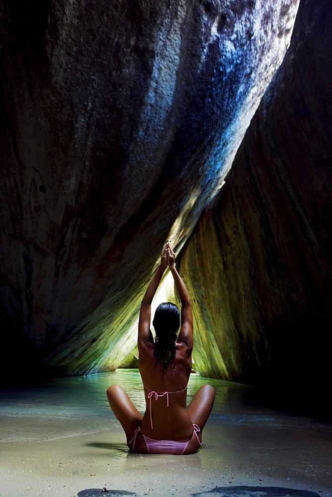Caribbean, British Virgin Islands, Virgin Gorda, The Baths, The Crawl, Woman doing yoga in sea cave.