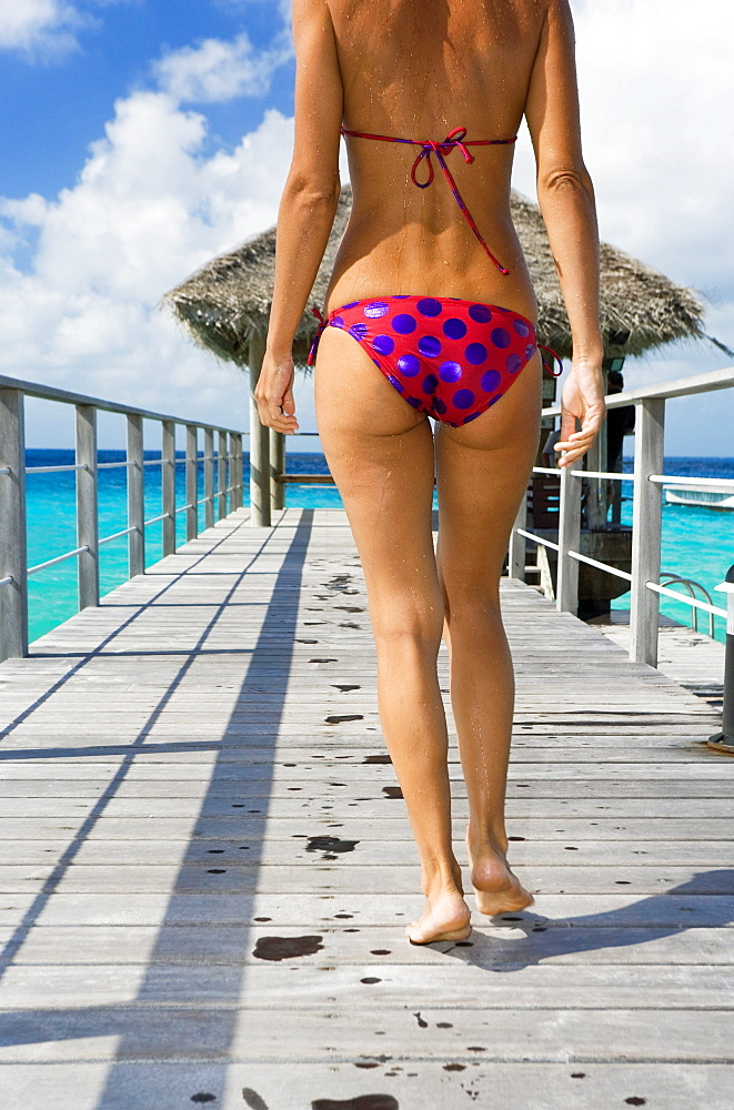 French Polynesia, Tuamotu Islands, Rangiroa Atoll, Woman walking down ocean pier, View from behind.