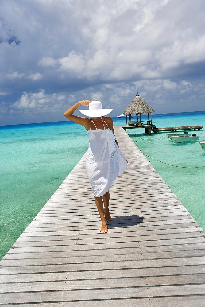 French Polynesia, Tuamotu Islands, Rangiroa Atoll, Woman in white walking on ocean pier.