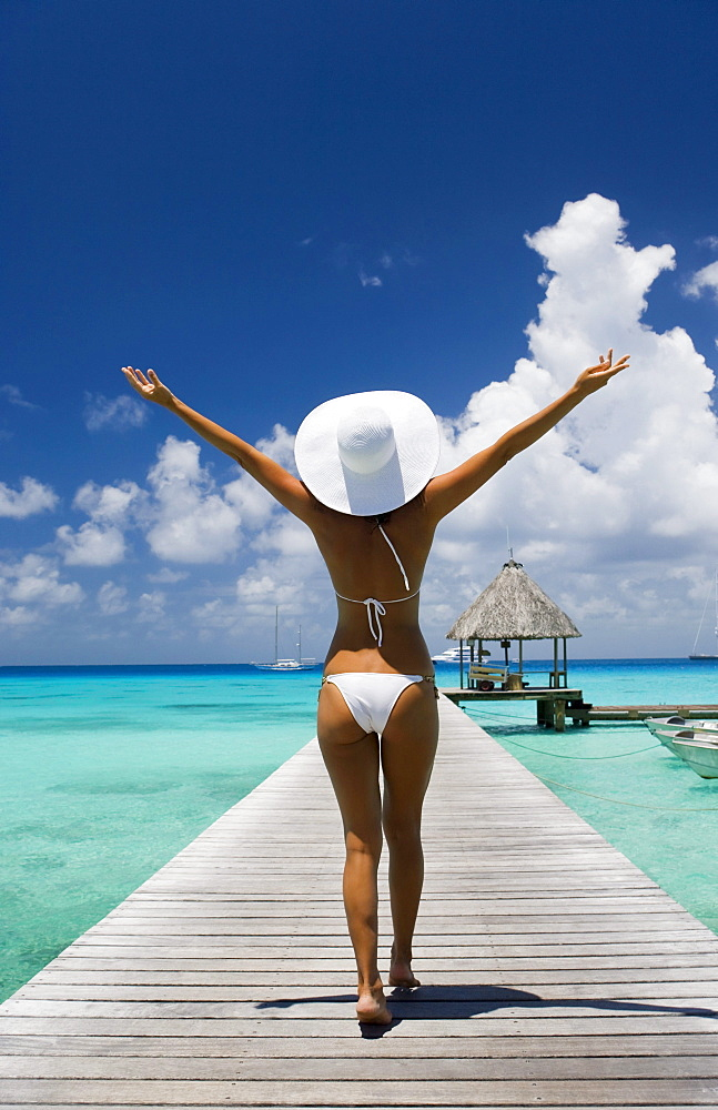 French Polynesia, Tuamotu Islands, Rangiroa Atoll, Woman walking down ocean pier, View from behind.
