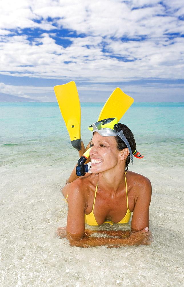 Woman wearing snorkel gear near ocean's edge.