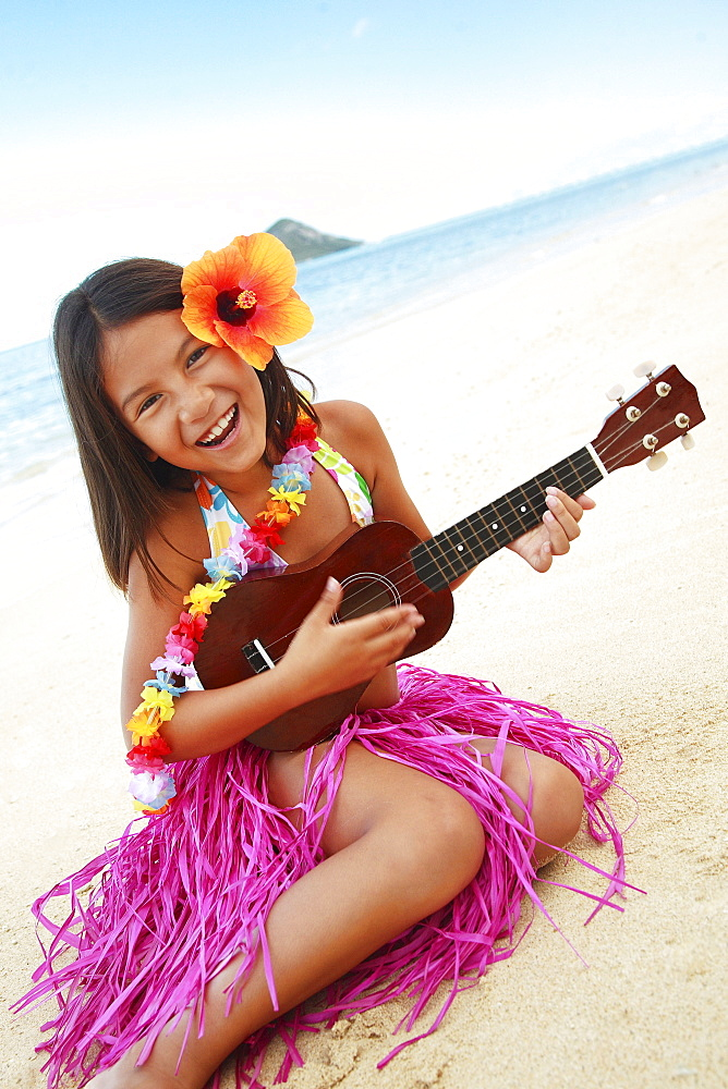 Hawaii, Oahu, Young girl smiling and playing ukulele on the beach in a hula skirt.