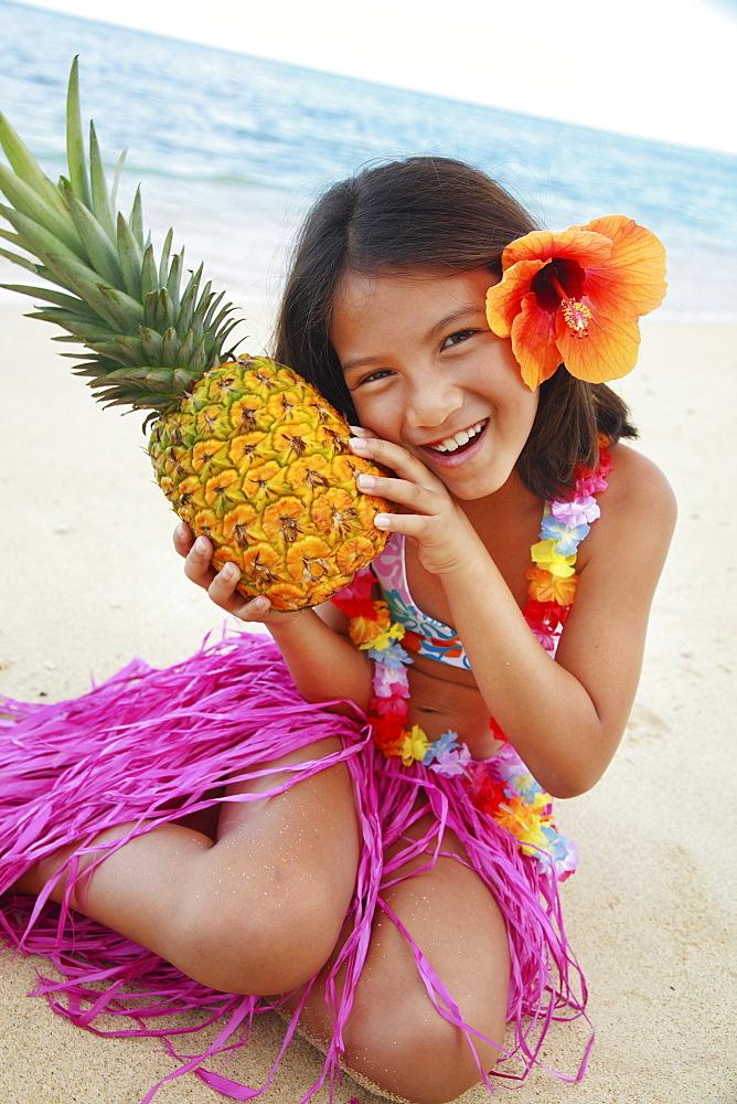 Hawaii, Oahu, Young girl holding a pineapple.