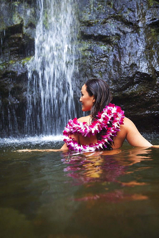 Hawaii, Oahu, Manoa Falls, Beautiful female with orchids leis sitting in a pond at the bottom of Manoa Waterfalls.