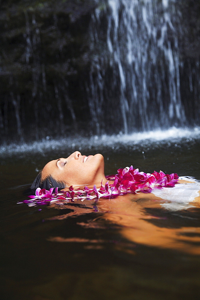 Hawaii, Oahu, Manoa Falls, Beautiful female with orchids leis floating at the bottom of Manoa Waterfalls.
