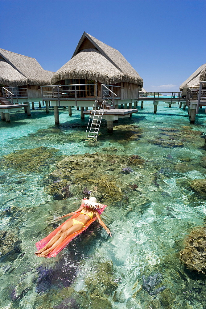 French Polynesia, Moorea, Woman sunbathing on inflatable raft over ocean reef, Luxury resort bungalows over ocean.