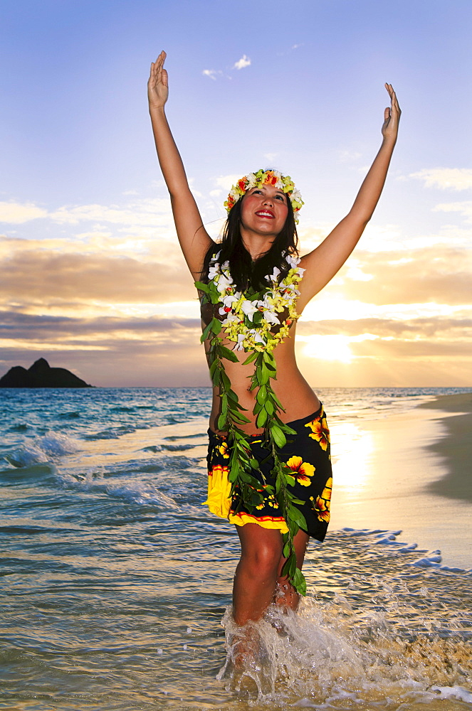 Hawaii, Oahu, Lanikai, Female hula dancer along beach shoreline at sunrise.