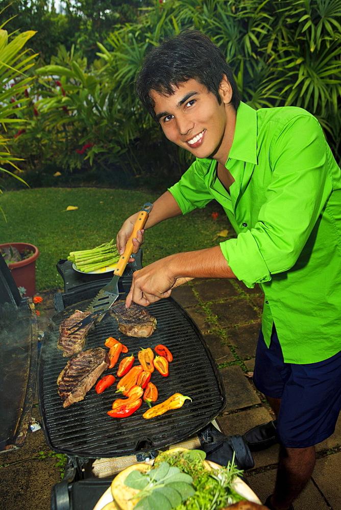 Hawaii, Young man preparing Outdoor barbecue feast in Hawaii garden.