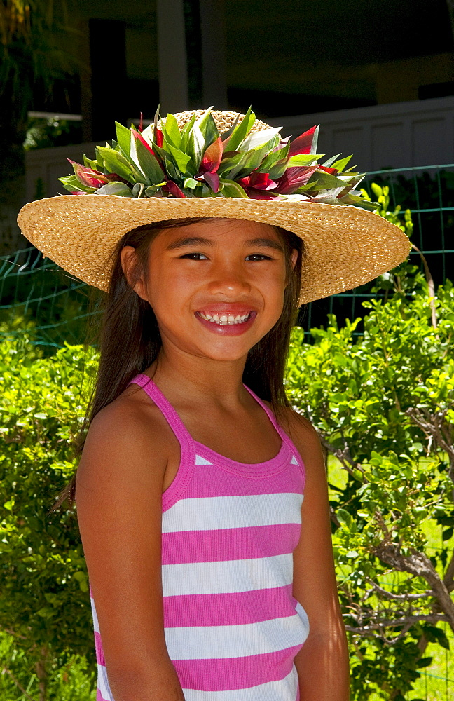 Hawaii, Oahu, Honolulu, Local young girl models a straw hat in her portrait.