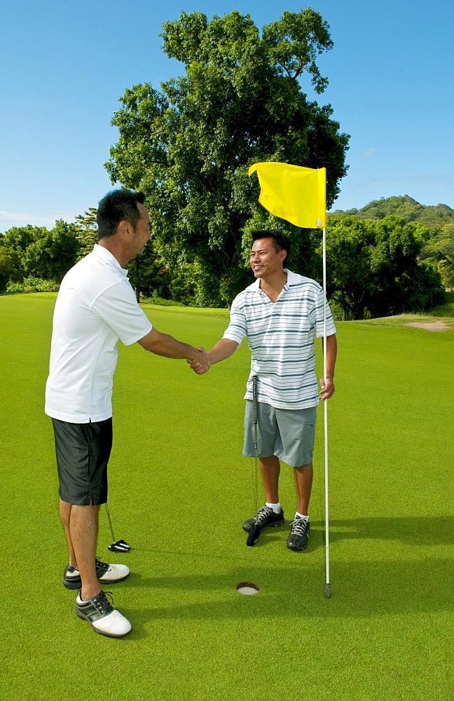 Hawaii, Oahu, Honolulu, Pali Golf Course, A local golfer congratulates his friend after making a good shot at hole 5.