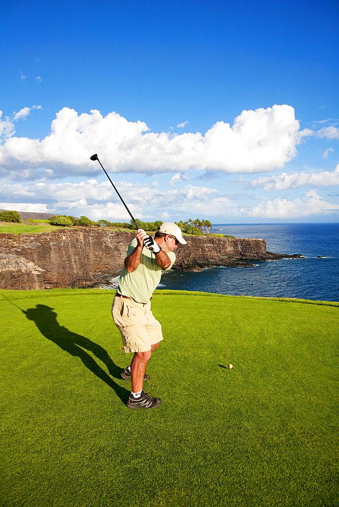 Hawaii, Lanai, Man hitting a tee shot on The Challenge at Manele golf course.