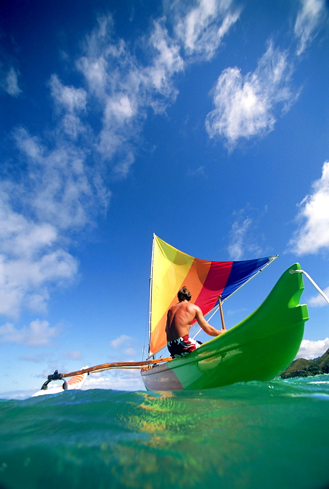 Hawaii, Oahu, Lanikai, Man in colorful sailing canoe. - 1116-28618