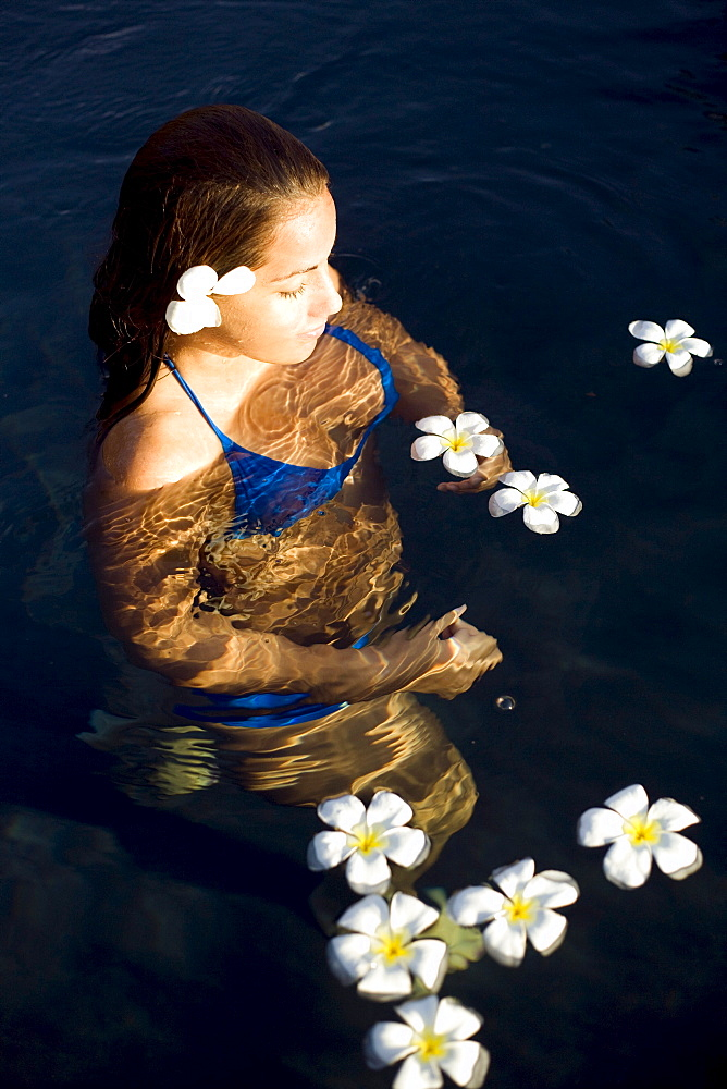 Hawaii, Oahu, Young woman relaxing in tropical pool with plumerias.
