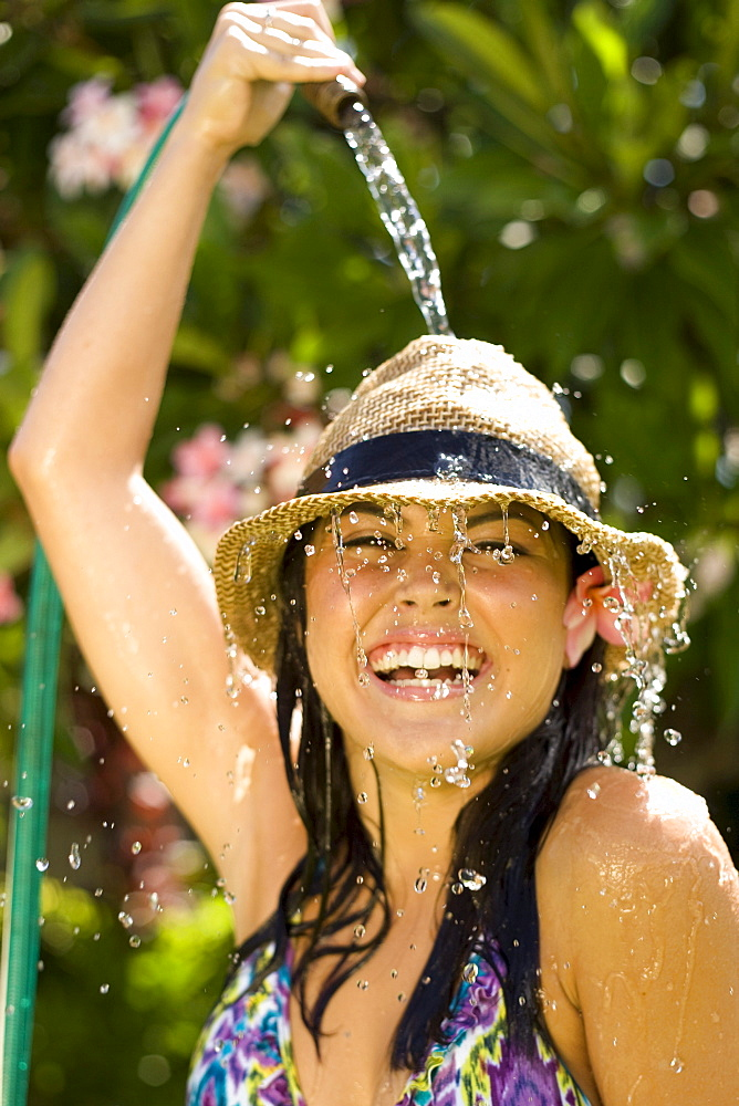 Hawaii, Oahu, Young girl splashing water on herself with hose.