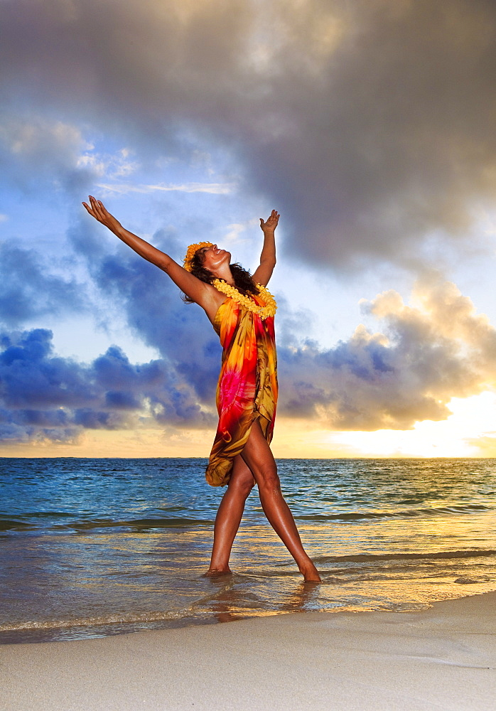 Hawaii, Oahu, Lanikai, Beautiful Hawaiian woman dancing hula on ocean shoreline.